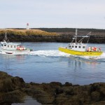 Fishing boats heading past Peter Island lighthouse at Brier Island